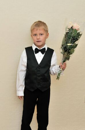 elegant little boy holding roses, he is going to school at his first time photo