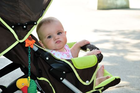 funny baby is sitting in her stroller