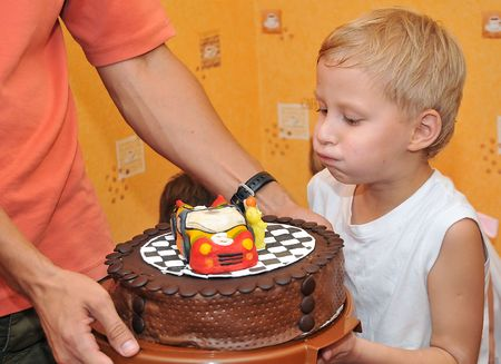 boy  blowing out candles on birthday cake, he already is 6 years old photo