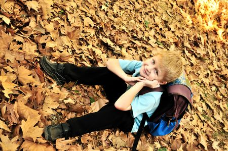 Child resting in a park amongst autumn leaf fall after school Stock Photo - 5617423