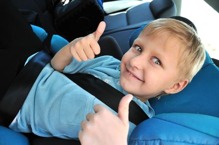 little schoolboy using child safety seat, he showing thumbs up