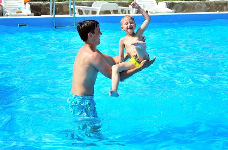 father fling in  his little son in the pool, they are smiling, they are happy photo