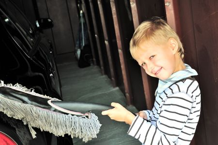Young boy cleaning his dad's dark car in  garage Stock Photo - 5676439