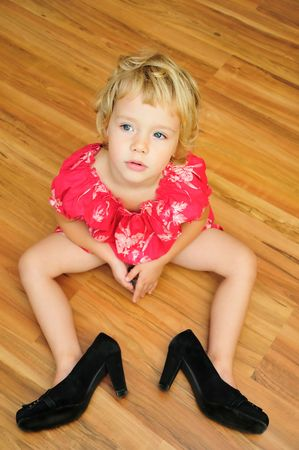 little girl is sitting on the flour, she is wearing mother's high-heels shoes, snappy dresser Archivio Fotografico