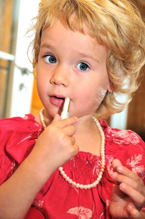 little girl using lipstick, she is wearing necklace