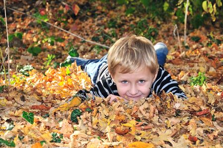 boy is laying in the forest in fallen leaves photo