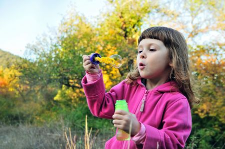 little girl blowing soap bubbles to   windward in the forest photo