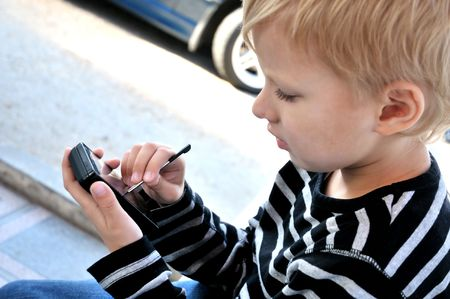 little boy using smartphone with stylus photo
