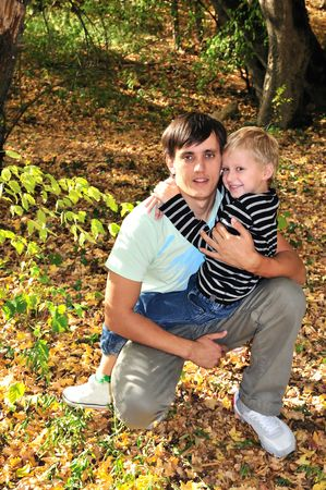 boy embracing his father in the forest in fall time Stock Photo - 5740385