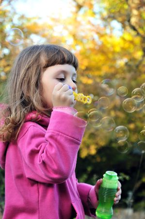 little girl blowing soap bubbles in autumn forest photo
