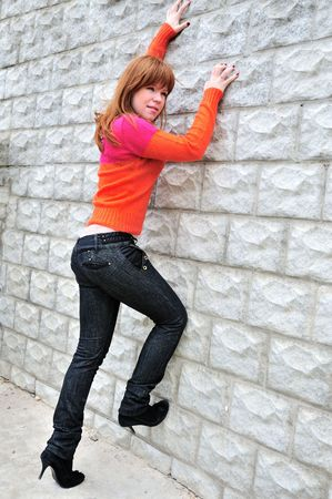 wanting: fashion girl wanting to climb the wall Stock Photo