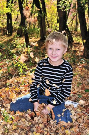 boy playing with yellow maple leaves in the forest. photo