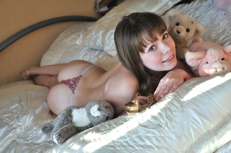 sexy girl laying in bed with her stuffed animal  photo