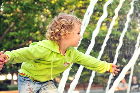 little blonde curved girl touching water of   fountain photo