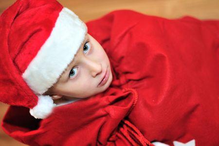 present from Santa - little Santa helper in red bag photo