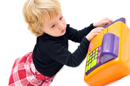 toddler girl playing with  cash register over white   photo