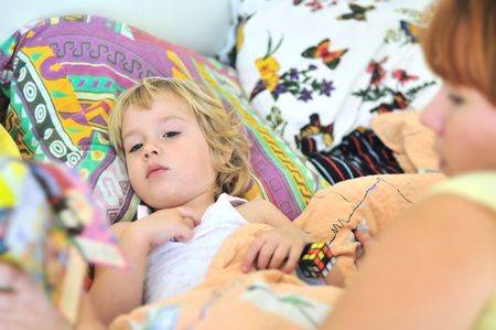 mother reading book for daughter before dream photo