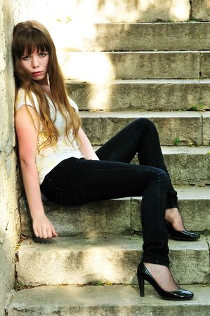 sad lonely girl: sad lonely girl sitting on the stairs Stock Photo