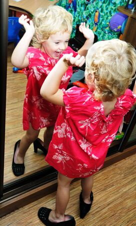 little girl happy to see herself wearing new dress in mirror photo