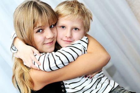Fratello e sorella a casa sorridente e abbracciando Archivio Fotografico - 6046382