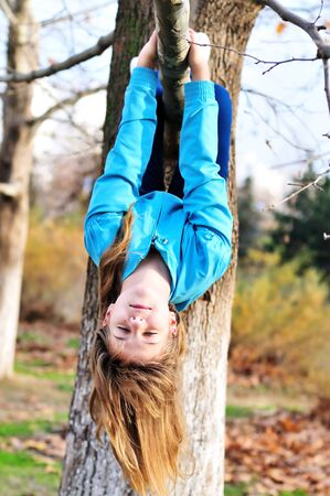 hanging woman: Teen girl hanging on the tree in  autumn time like a sloth