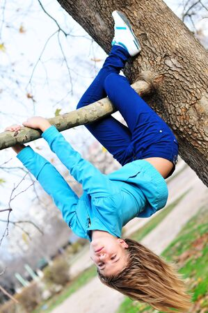Teen girl hanging on the tree in autumn time, like a sloth. photo