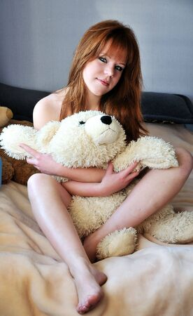 pretty redheaded girl sitting on the bed  photo