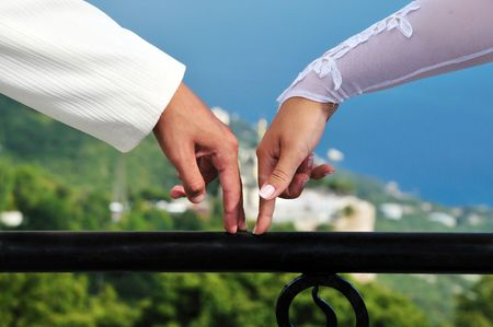 marriageable: fingers of bride and groom going towards each other over wonderful view