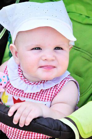 lovely baby girl sitting in the stroller  photo