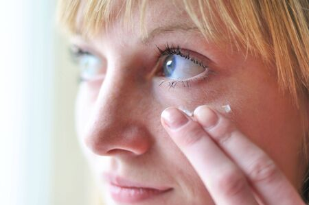 face of girl applying cosmetic cream on skin around eyes - soft focus