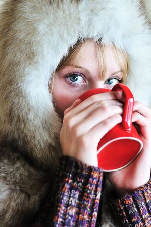 Girl in fur cap drinking tea from red cup  photo