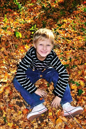 happy boy sitting in leaves in sunny autumn forest photo