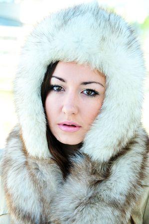 eyes hazel: pretty brunette with hazel eyes is wearing winter fur cap Stock Photo
