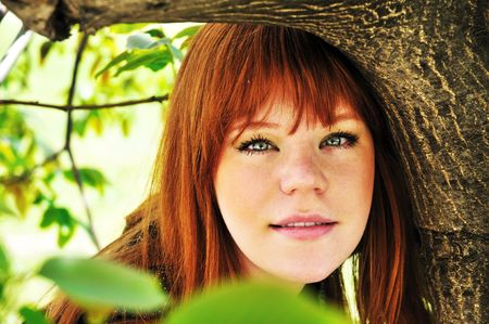 face of spring redheaded girl under the green tree photo