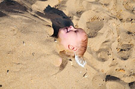 boy is laying under the sand on the beach photo