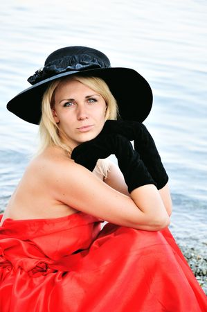 lady wearing red dress and black gloves and hat on the beach photo