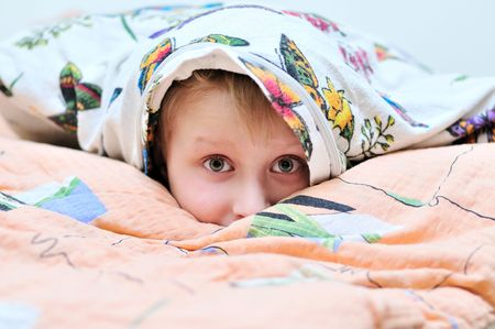 frightful: little boy laying under the pillow and watching something frightful on TV
