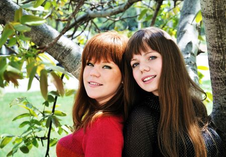 two lovely sisters in spring time under the tree photo