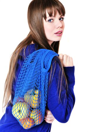 greengrocery: longhaired girl wearing blue sweater with fruit and vegatables after shopping in greengrocery with  string bag