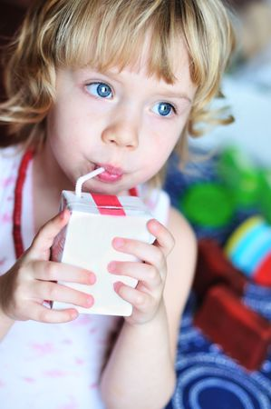 little lovely girl drinking juice from straw