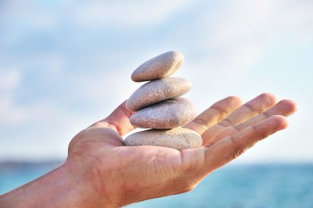 balancing stones in mans palm over blue sky