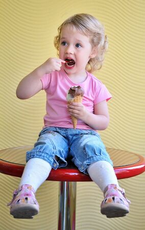 ice cream stand: little funny blonde girl eating big ice cream
