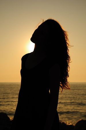silhouette of sunset girl at the beach Stock Photo