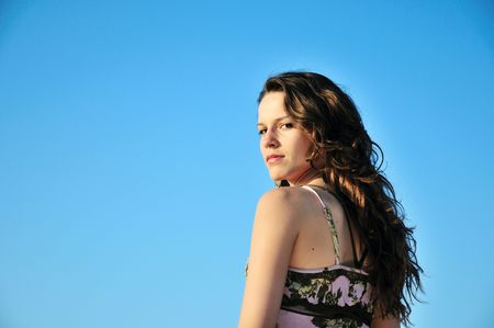 pretty  brunette longhaired girl over the blue sky   photo