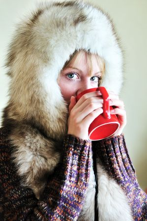 Girl in fur cap drinking tea from red cup Stock Photo - 6617902