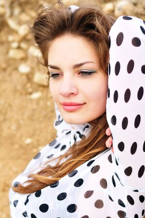 beautiful young girl wearing spotted blouse outdoors photo