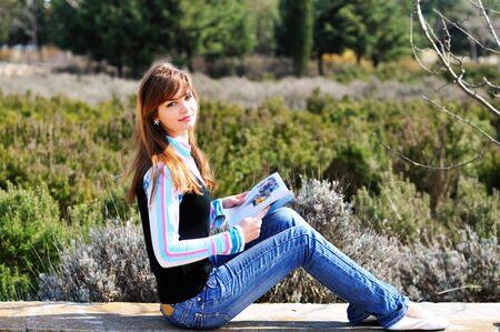 fashion teen girl  resting in park and reading magazine Stock Photo - 6711063