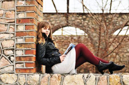 teen girl reading magazine outdoors on the window Stock Photo