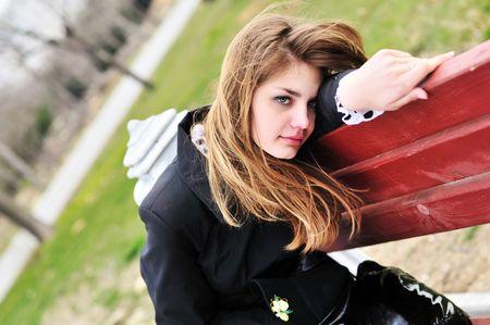 fille triste: fille triste sur le banc dans le parc. Banque d'images