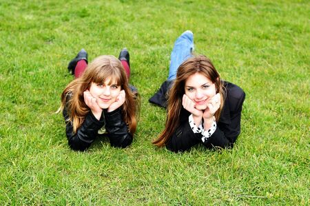 two lovely teen girls laying on the green grass  photo
